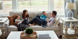 A family lounges on a couch beside big windows.