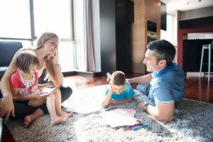 A family lounges on a rug as kids play.