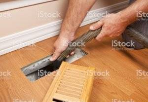An air duct is vacuumed clean.