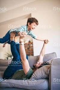 A father plays with his son on a couch.