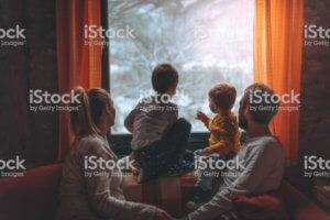 A family gathers around a window to look outside at snow.