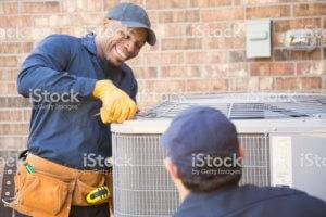 Two technicians work to repair an AC Unit.
