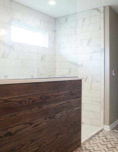 A view of a new shower stall with glass and wood paneling.