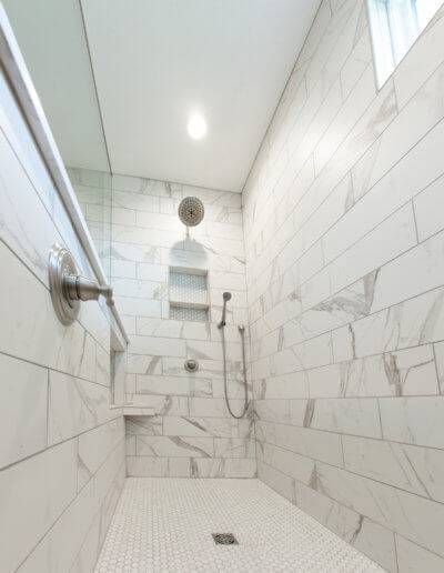 The inside of the new white tiled and marbled shower.