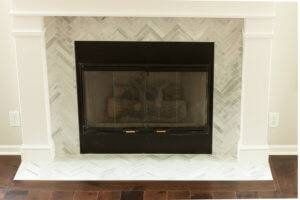 A photo of a remodeled fireplace with white tile.