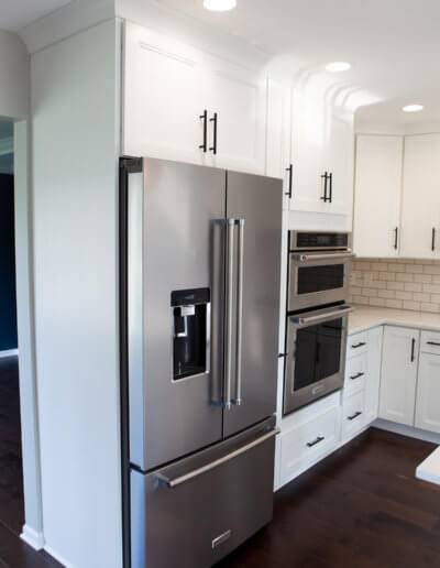 Kitchen with white cabinets and stainless steel fridge and double wall oven.