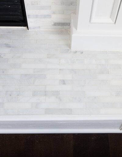 custom fireplace hearth with thin white tiling