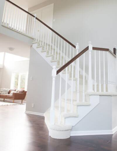 custom staircase with brown hand rail and white posts and carpeted stairs