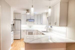 A white kitchen remodel with white countertops, cabinets, and stainless steel appliances.