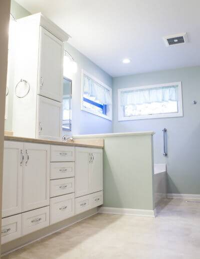 A photo of an extended bathroom including a spa and white cabinets.