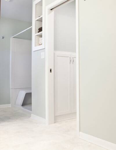 A photo of a linen closet, new shelving with white trim, and a shower stall.