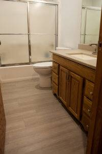 A photo of a shower, toilet, sink, and cabinets.