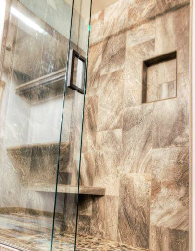 Walk-in shower with custom tiling and a sliding glass door.