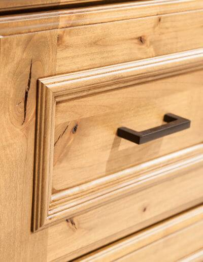 close up of wooden bathroom drawer with black hardware