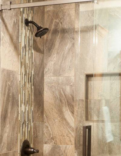 walk-in shower with a glass sliding door and custom tiling