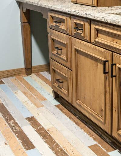 close up of a rustic bathroom floor and wood cabinets