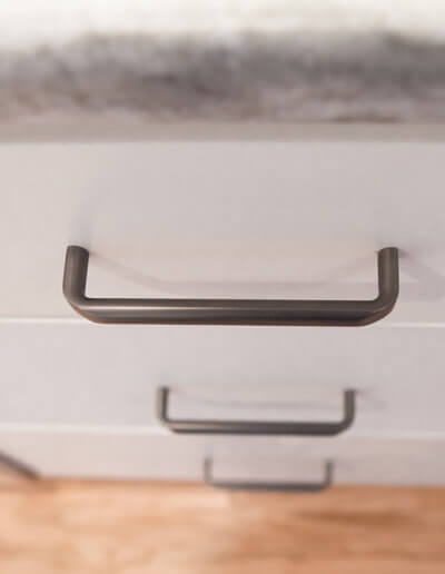 White kitchen drawer with a black handle.