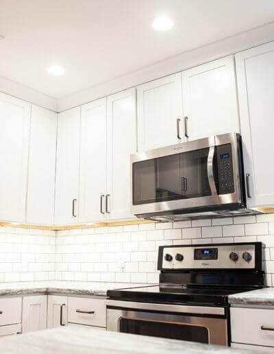 Kitchen with white cabinets. Black and stainless steel microwave and stove.
