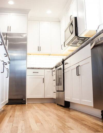 floor level view of a kitchen with an island. Complete with white cabinets and stainless steel appliances