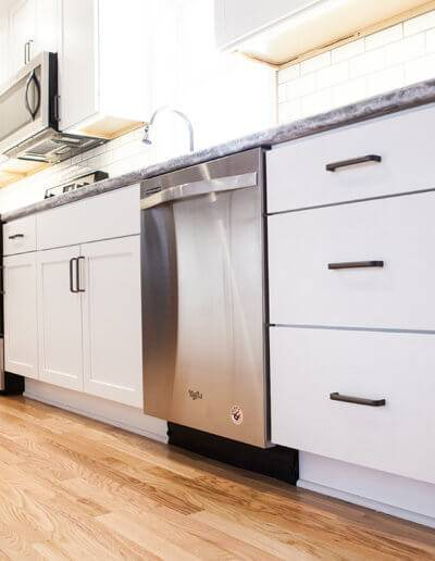 White kitchen drawers with black hardware. Silver Whirlpool dishwasher.