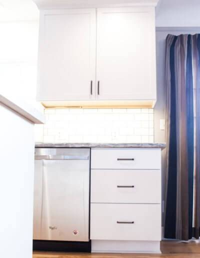 White kitchen drawers and cabinets. Under-cabinet lighting is turned on lighting up the subway tile backsplash