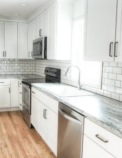 kitchen counter top with white and gray marbling and a subway tile backsplash