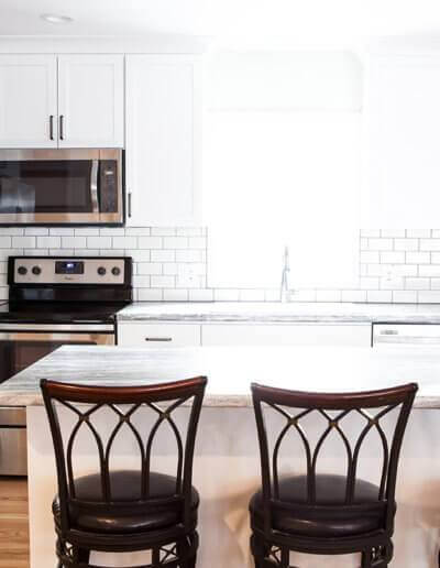 natural light shining into a kitchen with three bar stool chairs placed at an island