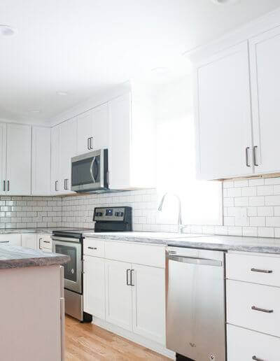 custom kitchen remodel displaying the island, subway tile back splash and sink