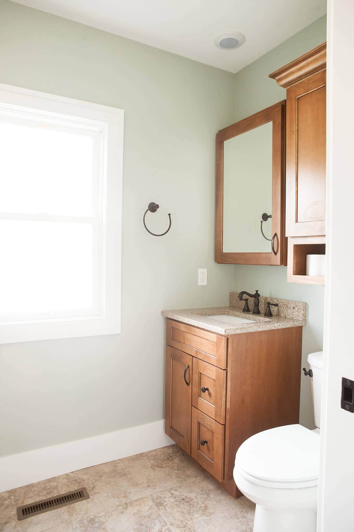 bathroom sink and mirror placed in the corner with a window letting in natural light