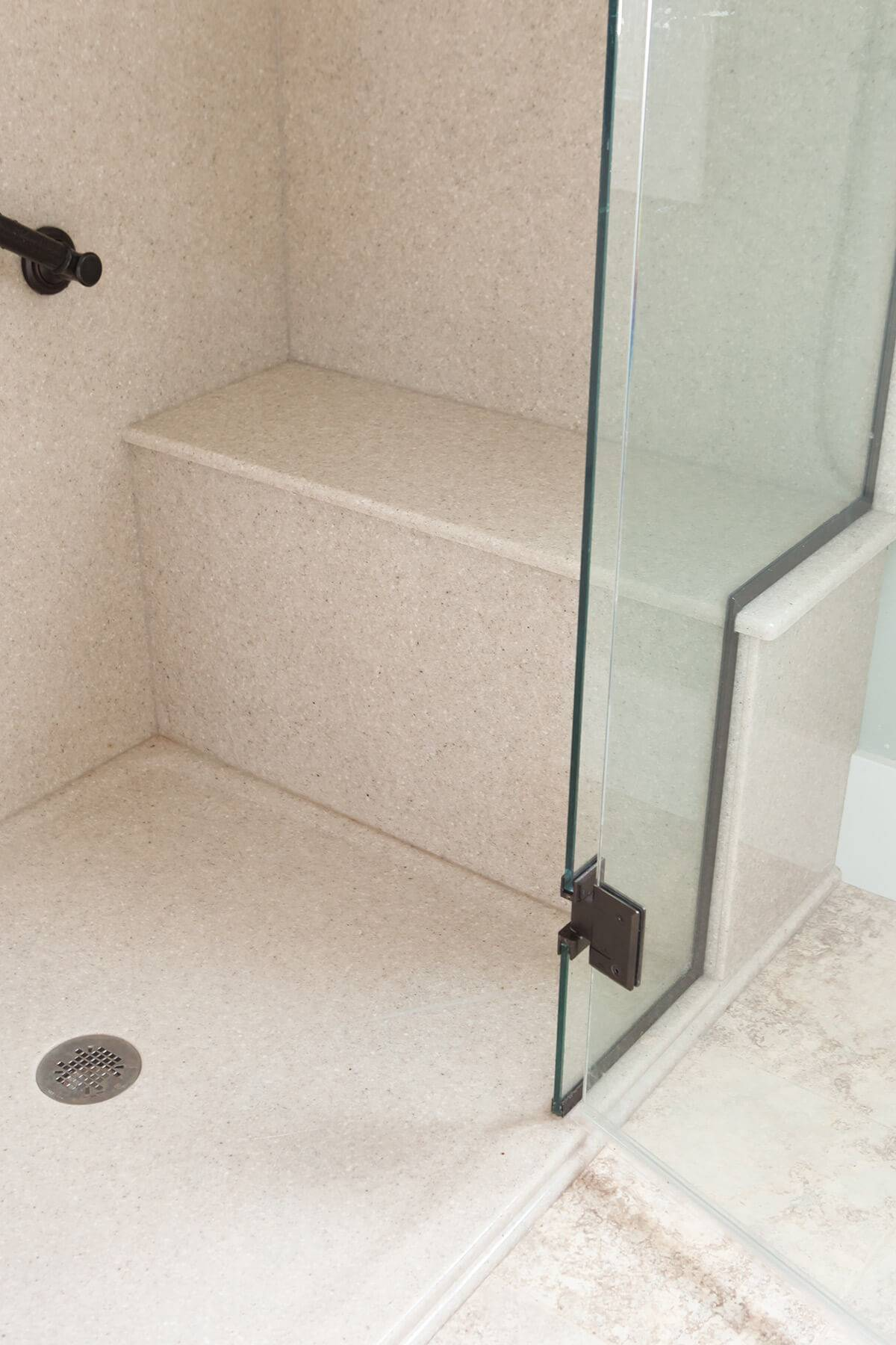 close up of walk-in shower with a bench