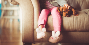 A child's feet hang over a couch with bunny slippers.