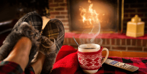 A photo of slippered feet and a coffee mug on a coffee table with a crackling fire in the background.