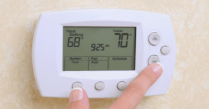 Someone changes settings on a wall-mounted thermostat.