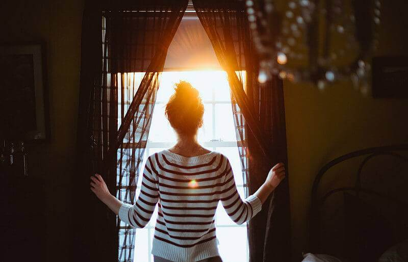 A woman opens the curtains in her home to let sunlight heat her house in the winter.
