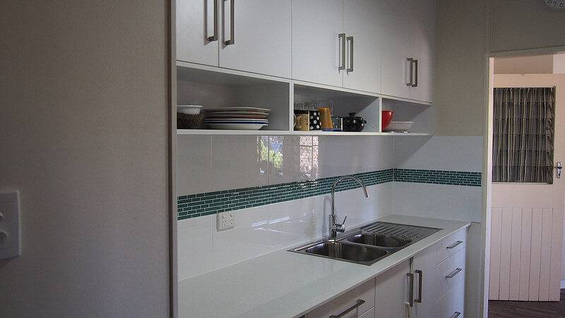 A remodeled kitchen with open shelving beneath the cabinets.