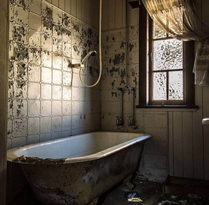 A photo of an old and dirty abandoned bathroom.