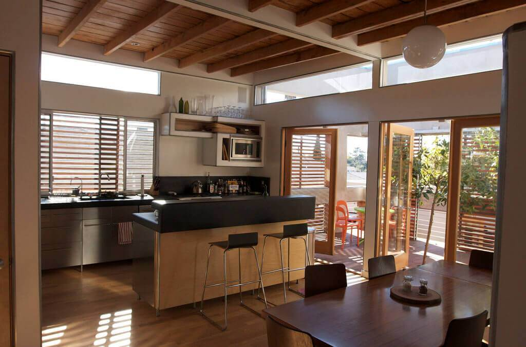An open kitchen with wooden rafters and industrial decor.