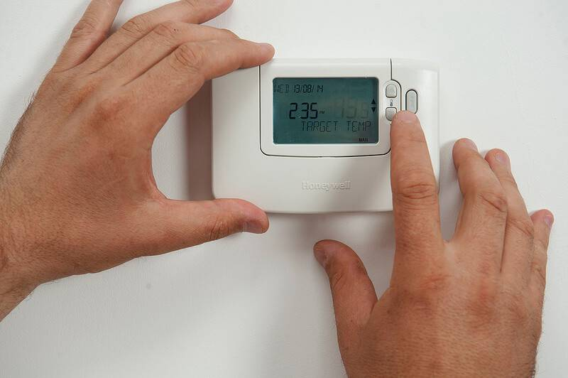 Hands adjust a thermostat on a wall.