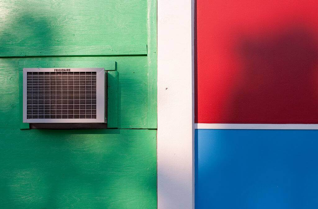 A picture of an AC window unit on a house with green siding.