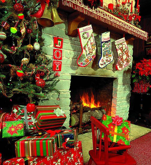 A fireplace with a tree and stockings nearby.