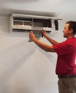 A Cyclone technician performs maintenance on a ductless AC unit.