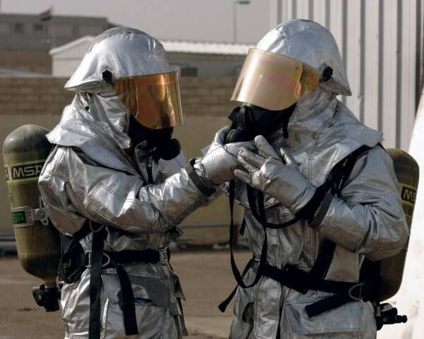 Two people in biohazard suits.