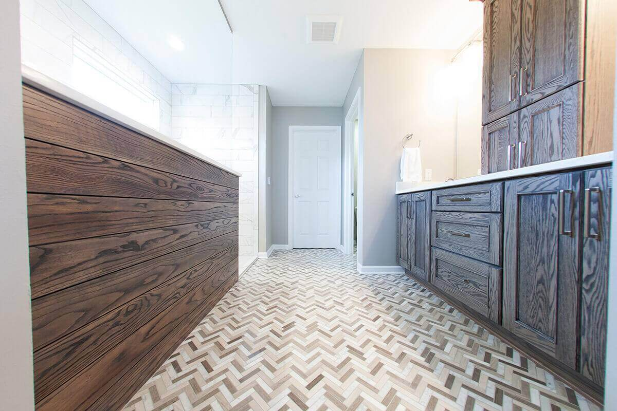 master bathroom with custom chevron tiled flooring and wooden cabinets
