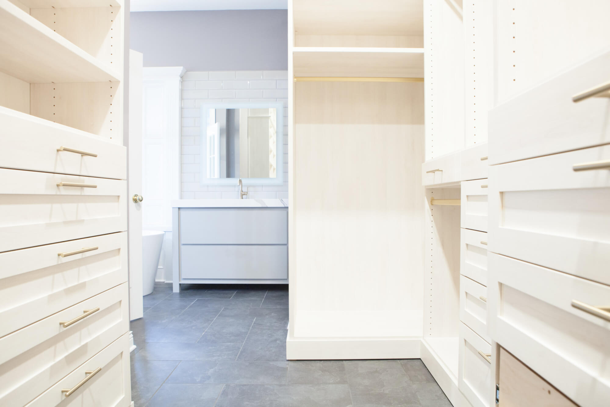 walk-in closest with custom built-in drawers and clothes hanging