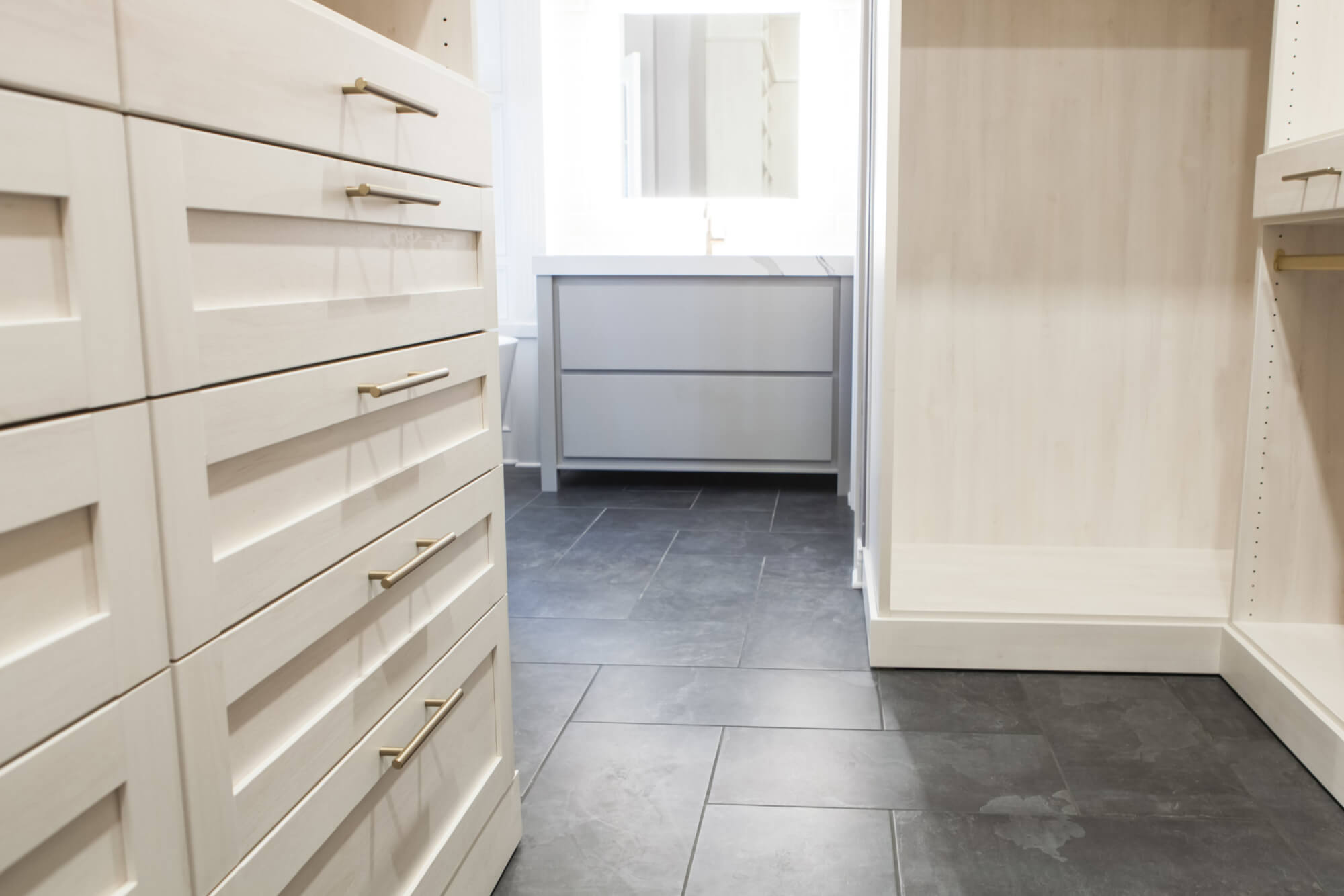 master bathroom closet area with custom built-in shelving and drawers