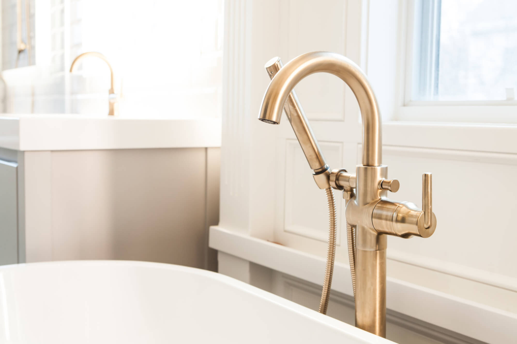 close up of brass bathtub faucet with handheld sprayer