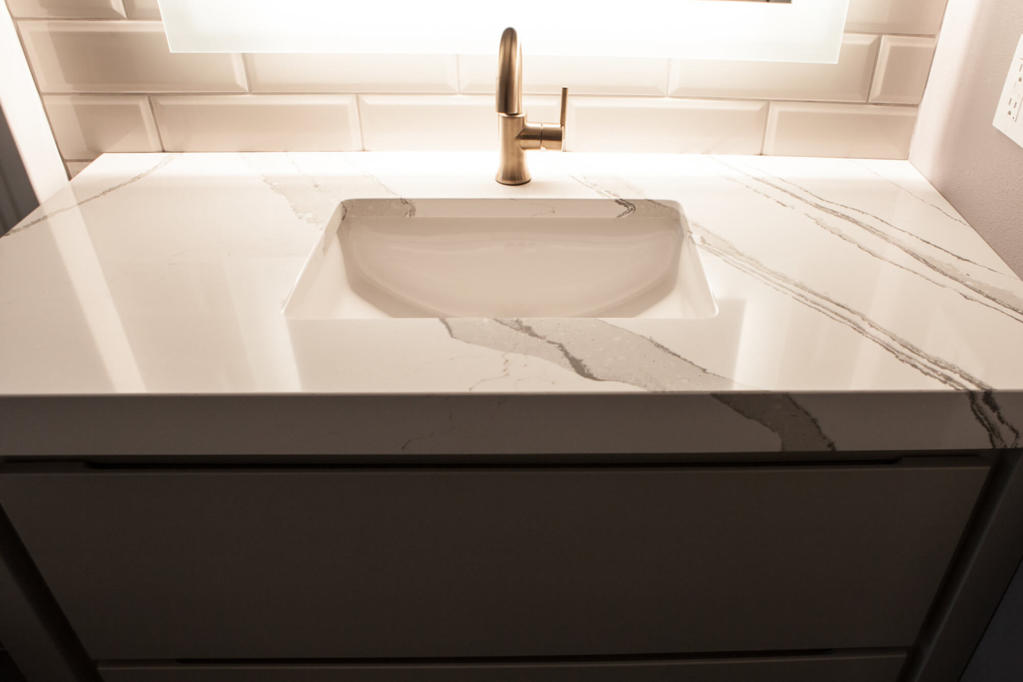 marble sink counter top illuminated by a light mirror