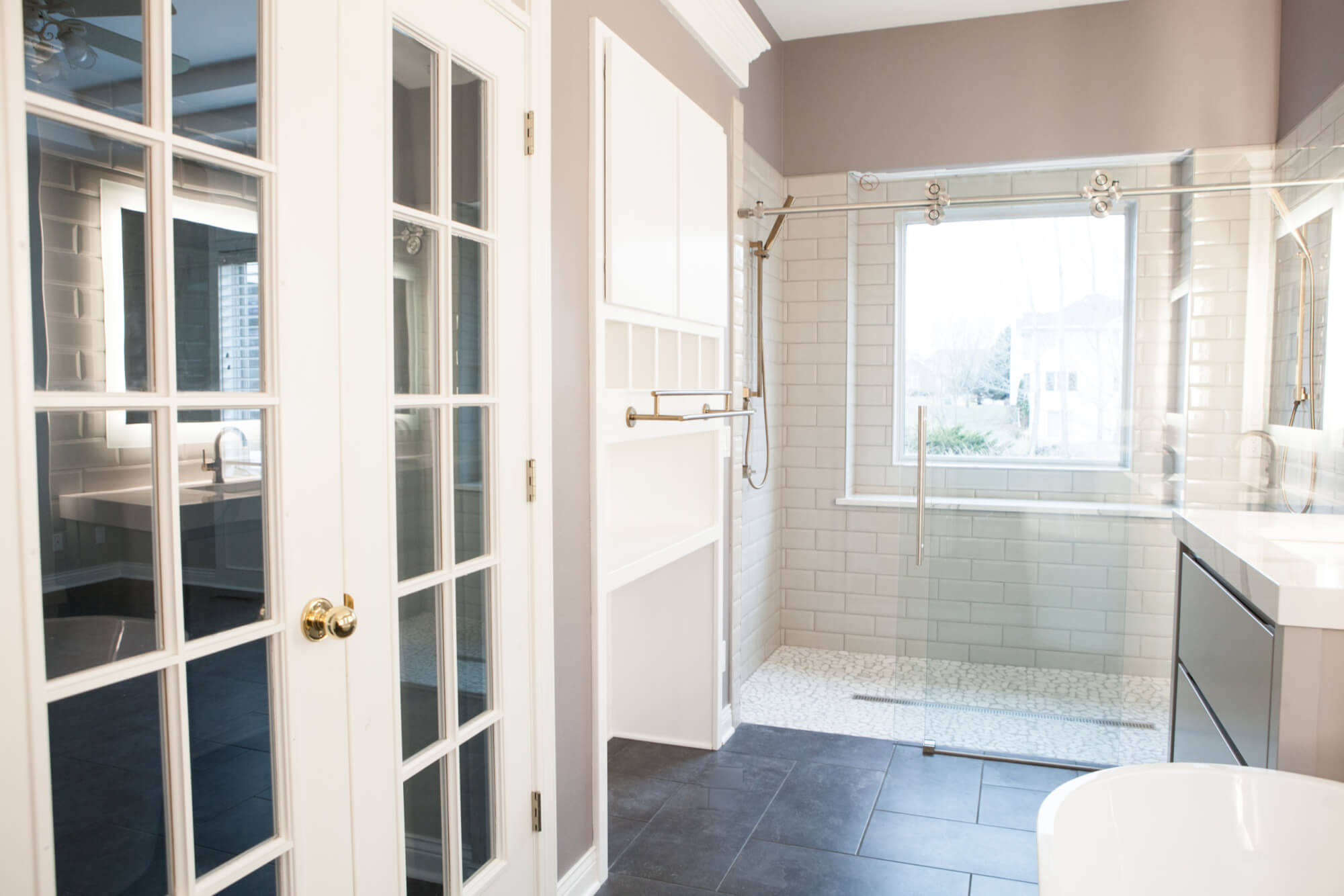 master bathroom with a large walk-in shower with a sliding glass door and built-in towel storage