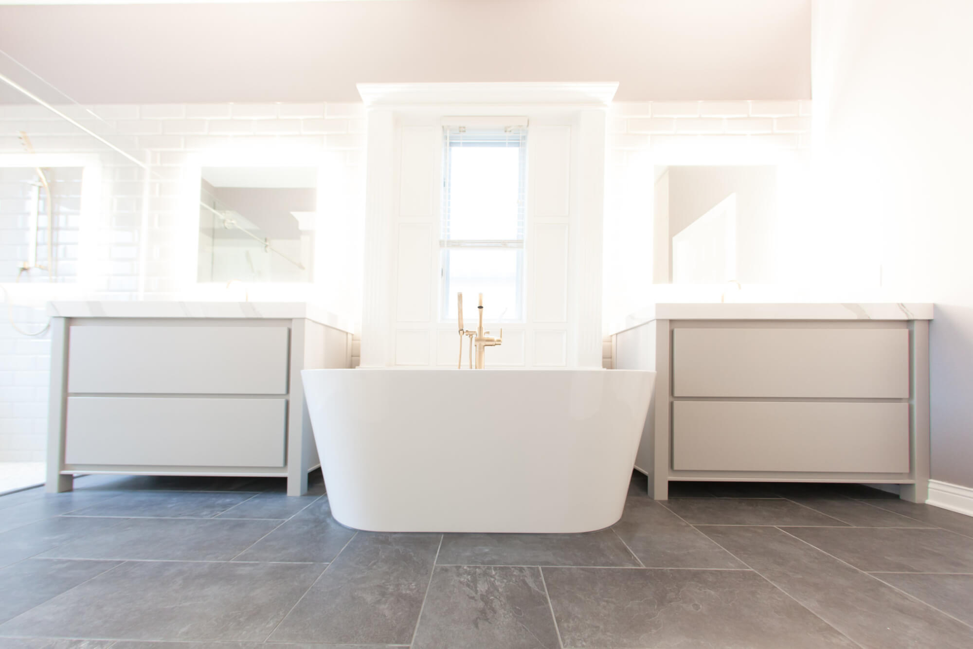 master bathroom with a drop-in bathtub between a his and her vanity