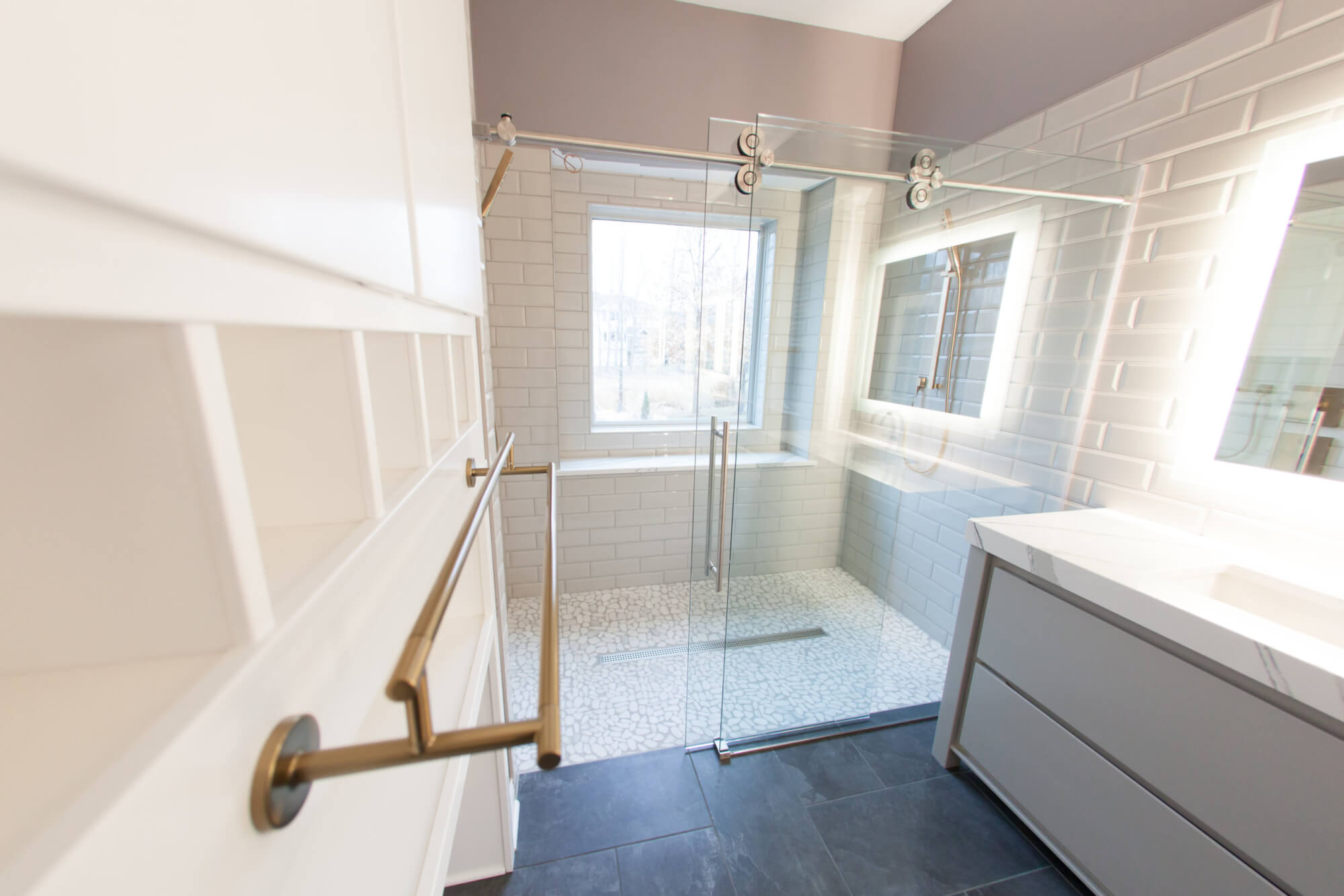large walk-in shower with a sliding glass door and custom floor tiling